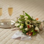 Edenton Weddings, flowers and champaign on the bed in the honeymoon suite