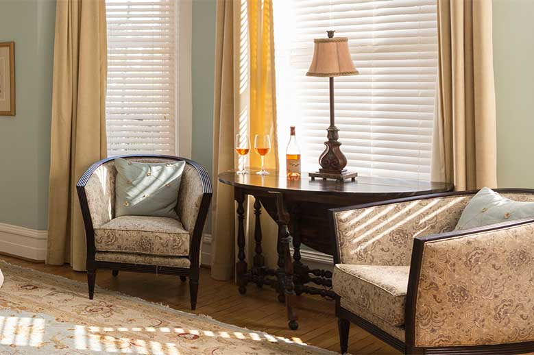 Close up of the two sitting chairs and drop-leaf table in the bay window in the Charles Eden Suite Inner Banks Getaway