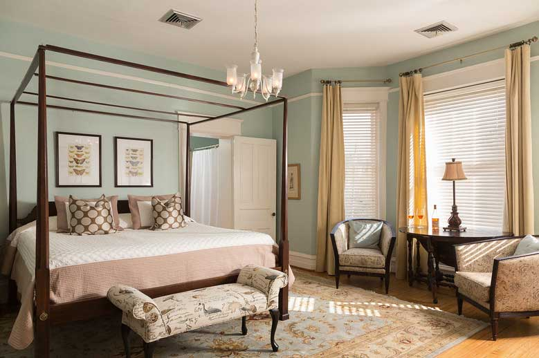 The Charles Edenton Suite at our Inner Banks Getaway with a view of the bed, open bathroom door, and two sitting chairs with table