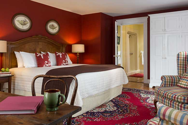 Romantic North Carolina Bed and Breakfast - Chowan Room with rich burgundy walls, showing bed and entrance to bathroom - ADA Accessible