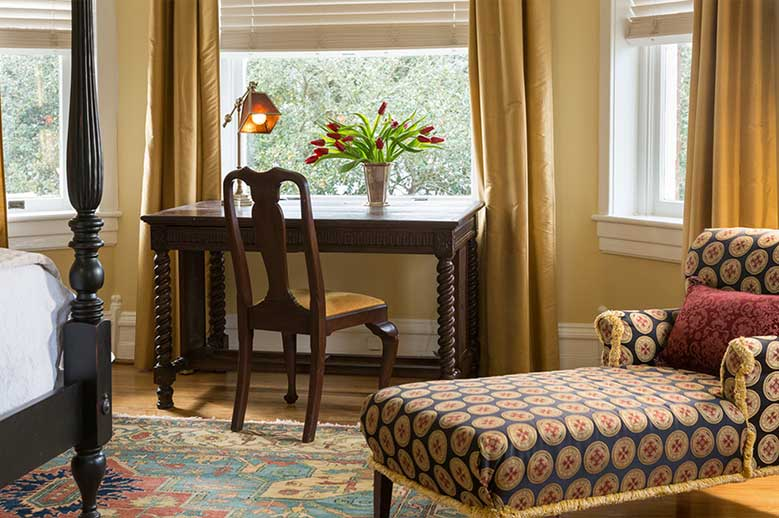 Close up the writing desk, chair and chaise lounge with views from our Edenton Hotel