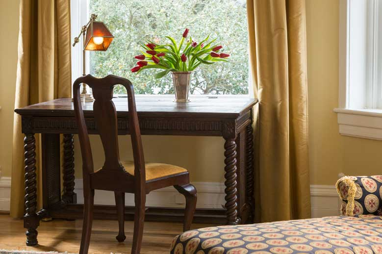 Antique writing desk with chair and desk lamp and vase of red tulips in the window at our Edenton Hotel