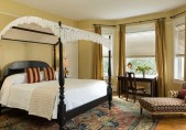 Daniel Earle Suite view of the four-poster bed, desk and chair and chaise lounge at our Edenton Hotel