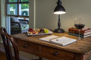 Drummonds Point Room in our Hotel in Edenton North Carolina - antique desk with fruit and cheese plate and glass of wine