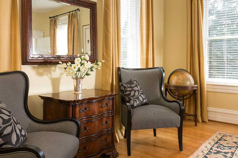Two sitting chairs with antique bureau in the middle in the Inglis Fletcher Suite at our Edenton B&B