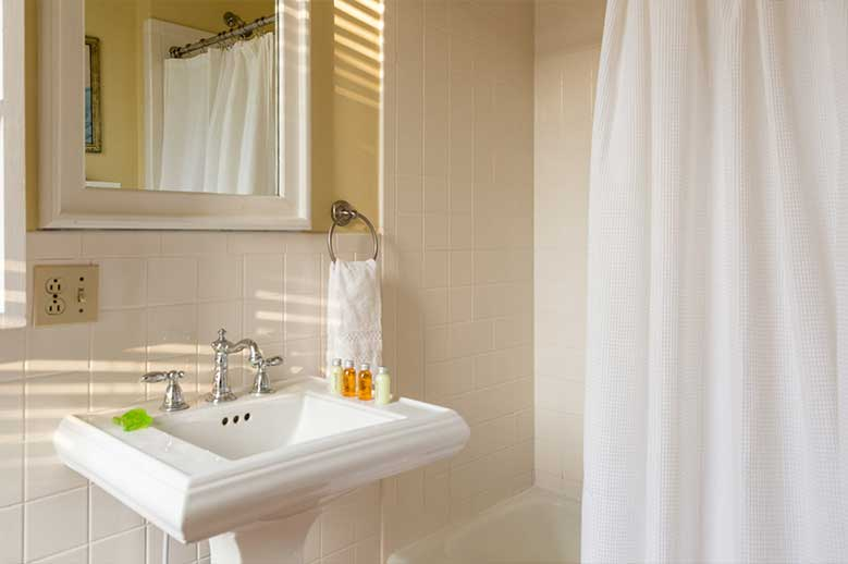 Bathroom, pedestal sink, shower and bathtub in the Inglis Fletcher Suite at our Edenton B&B