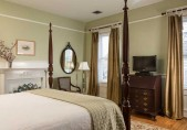 Our Joseph Hewes Suite - North Carolina Getaway view from the side of the bed. Fireplace, flat screen TV, two windows and antique bureau