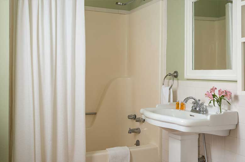 North Carolina Getaway B&B bathroom in the Joseph Hewes Suite, antique pedestal sink with bathtub and shower.