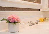 Flowers in the bathroom at our Bed and Breakfast room Penelope Barker Suite with soft focus background of sink