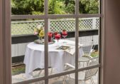 Boutique Hotels in Edenton NC, the Pembroke Room Bed view outside onto the patio with Sangria Drinks