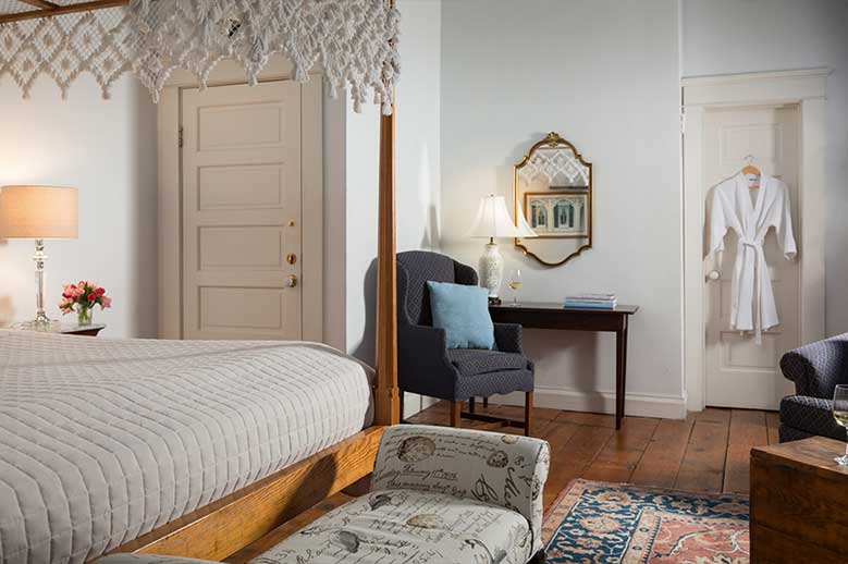 North Carolina East Coast B&B Queen Anne Suite looking from bed to bathroom door, highback chair and foot bench at bottom of the bed