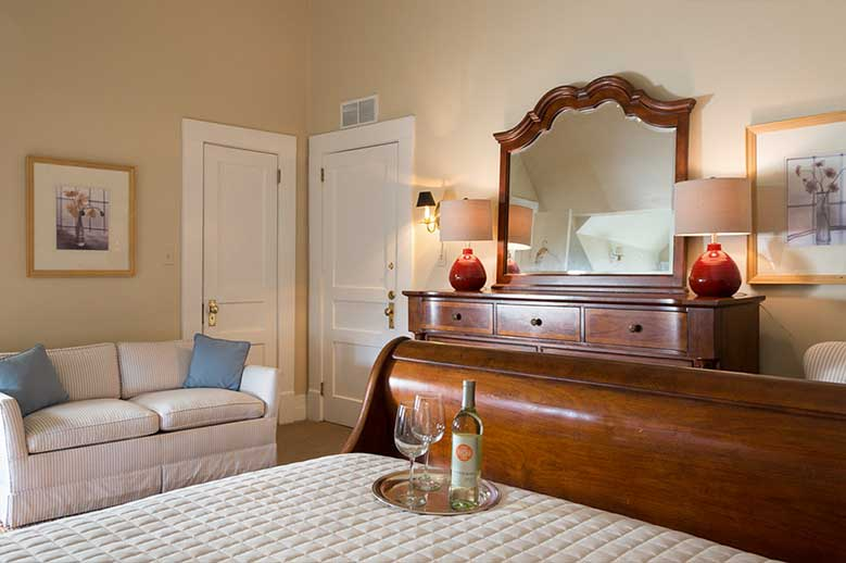 Edenton NC hotel Samuel T. Sawyer Family Suite, view of the bottom of the bed with tray with two wine glasses and a bottle of wine, antique bureau and two seater sofa