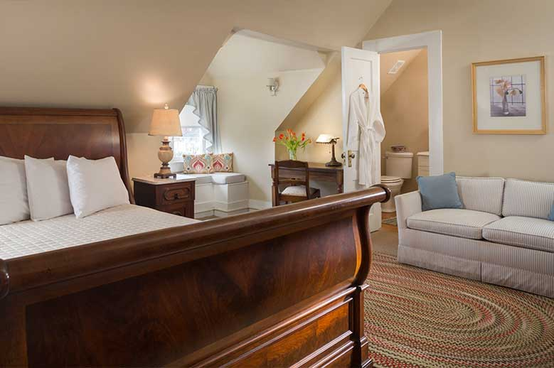 Edenton, NC hotel, view from the bottom of the sleigh bed, bathroom and two seater sofa in the Samuel T. Sawyer Suite