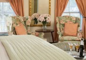 Romantic North Carolina Inn view from the foot of the bed, highback wing chairs, flowers in vase and big windows