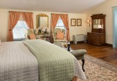 Romantic North Carolina Inn Sandy Point Suite, overview of room from side of bed, chairs, dresser and door to bathroom