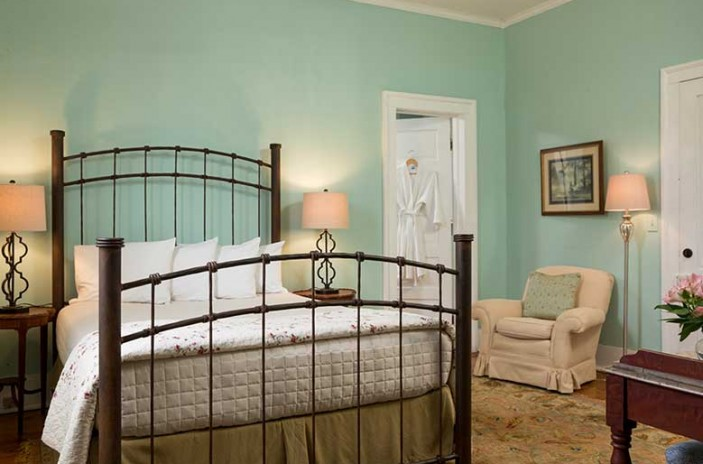 Romantic North Carolina Lodging Bedroom with iron frame bed, comfortable chair and bath robes
