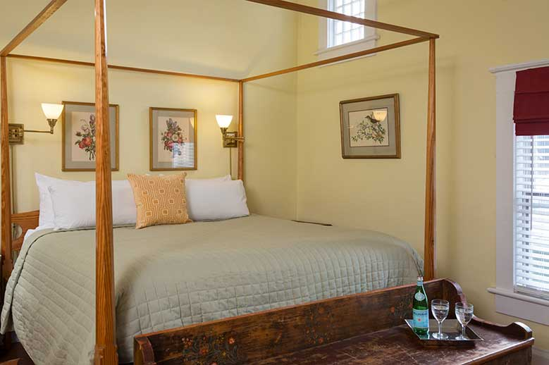Albemarle Suite, Romantic Getaways in North Carolina. View of the bed with water glasses on antique footer bench
