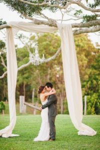 Bride and groom in garden under tree branch with material