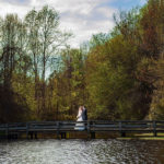 Bride and groom on the bridge with water and trees
