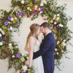 Bride and Groom in front of floral display