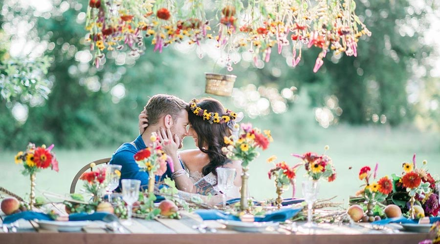 Elopements, couple at table decorated with many flowers - farm to table wedding