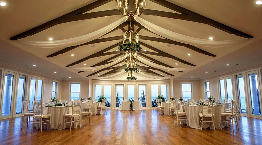 Wedding Venue, the great hall with surround windows and tables set up for a wedding event